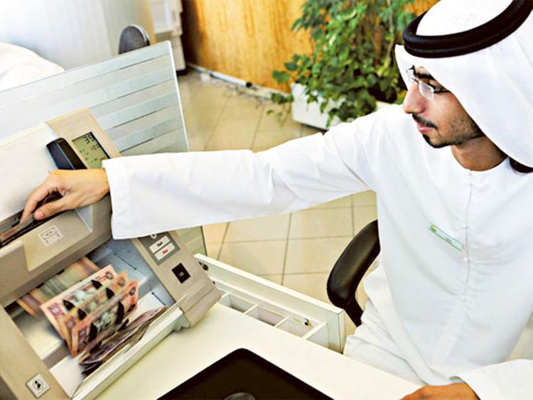 A teller counts dirham notes