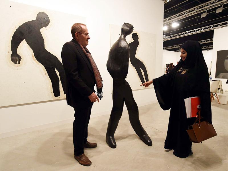 A visitor admires a bronze sculpture