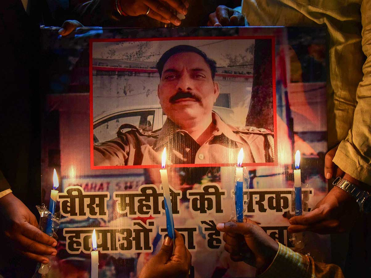 Samajwadi Party workers take part in a candle light march