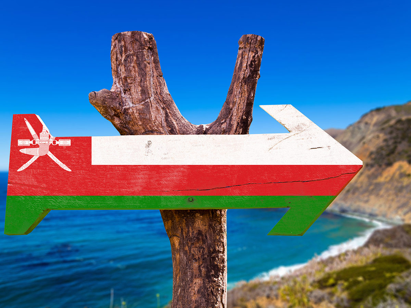 Oman flag sign with coast background.