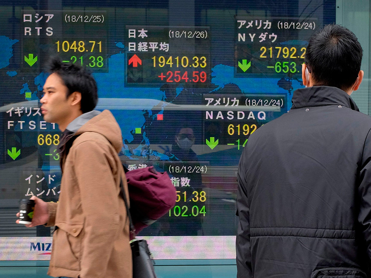 Pedestrians walk past a stock indicator