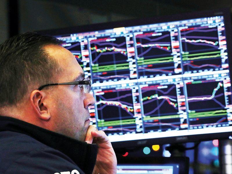 A trader looks at price monitors