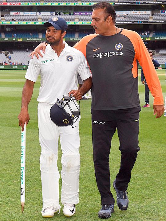 Mayank Agarwal (L) walks off with coach Ravi Shastri