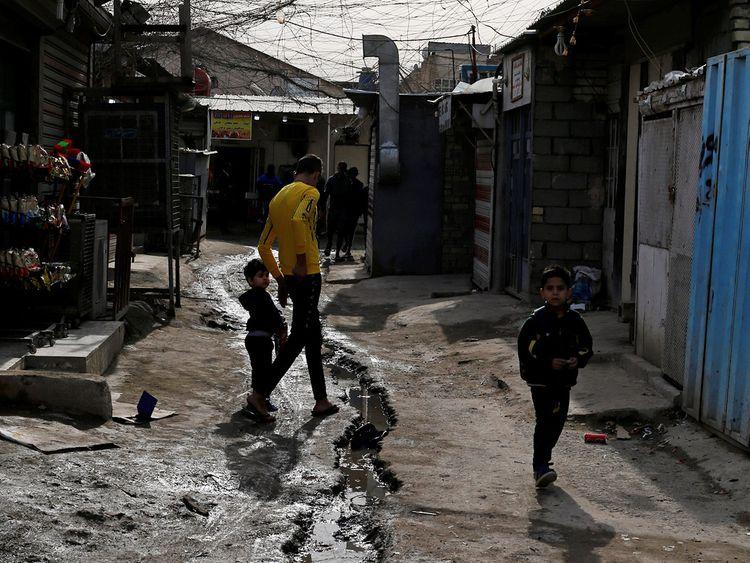 Palestinian refugees walk in a street in the Baladiyat