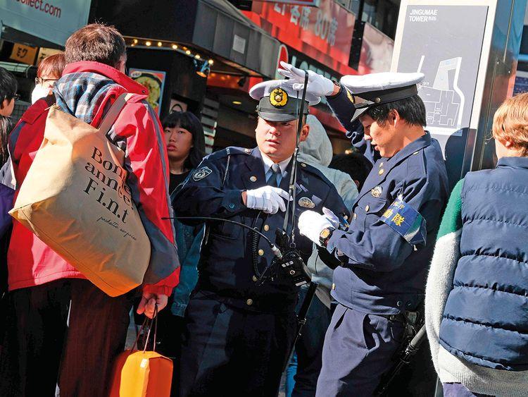 Policemen stand guard near Takeshita Street