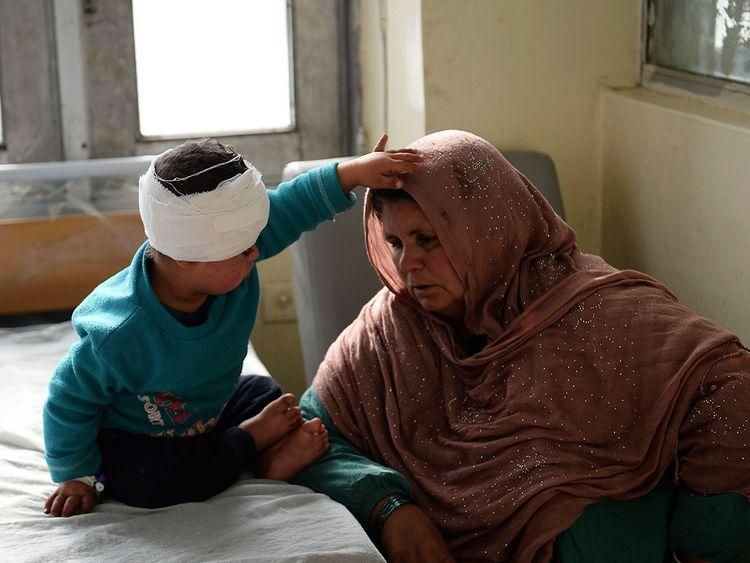An Afghan woman sits