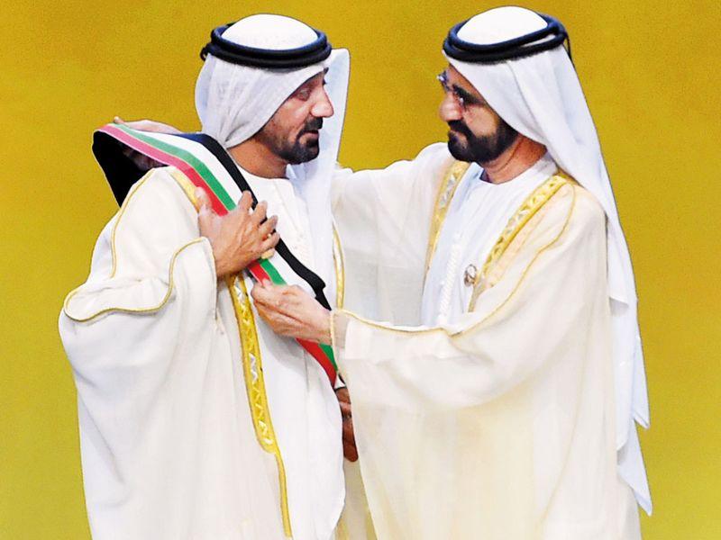 Shaikh Mohammad presents a sash to Shaikh Ahmad