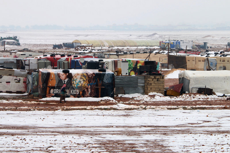 A Syrian refugee walks past makeshift shelters 091