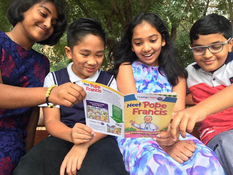 NAT_190117-Children-enjoying-a-copy-of-Meet-Pope-Francis-in-the-UAE-booklet-1547720298344