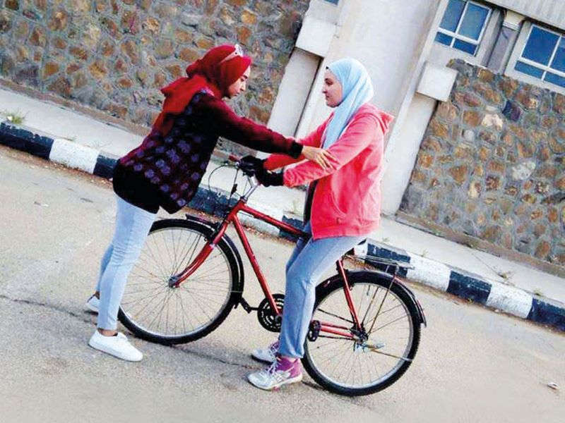 An Egyptian girl is being taught how to ride the bicycle.