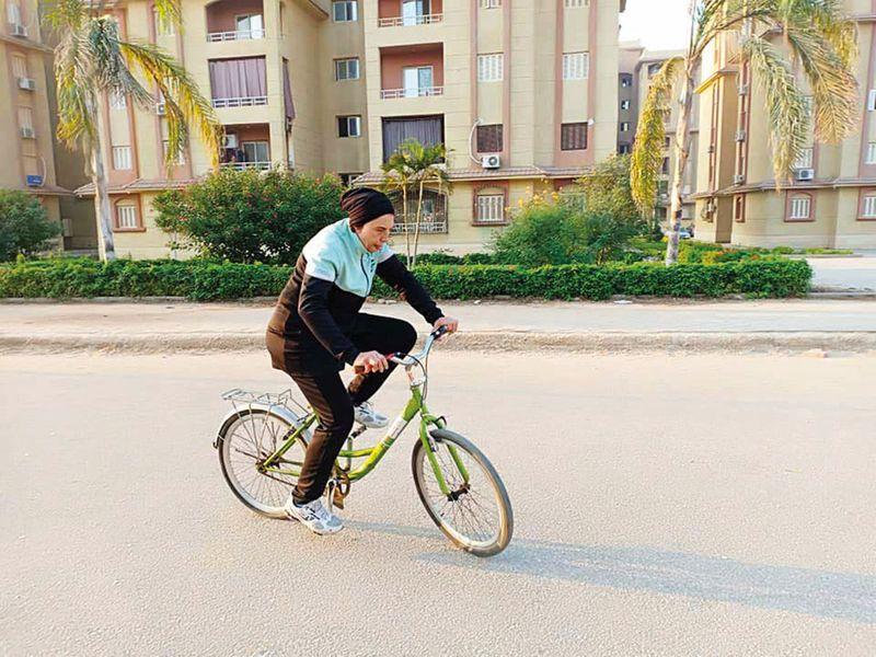 An Egyptian woman rides a bike.