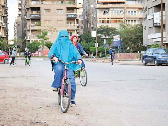 Women ride on cycles in a Cairo street.