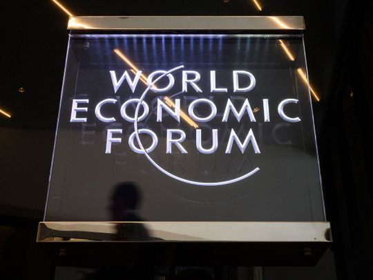 A man walks past a sign of the World Economic Forum