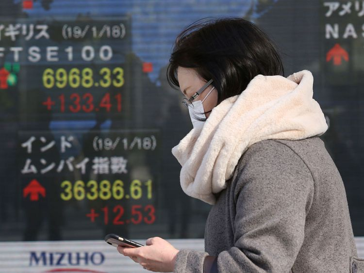 A woman walks by an electronic stock board of a securities firm in Tokyo