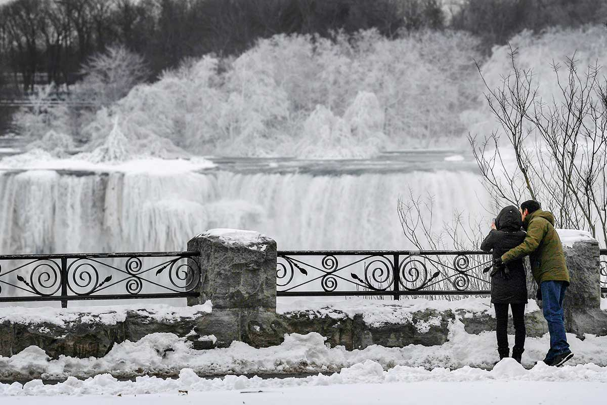 A couple takes a photo of ice formed on the American Falls in Niagara Falls