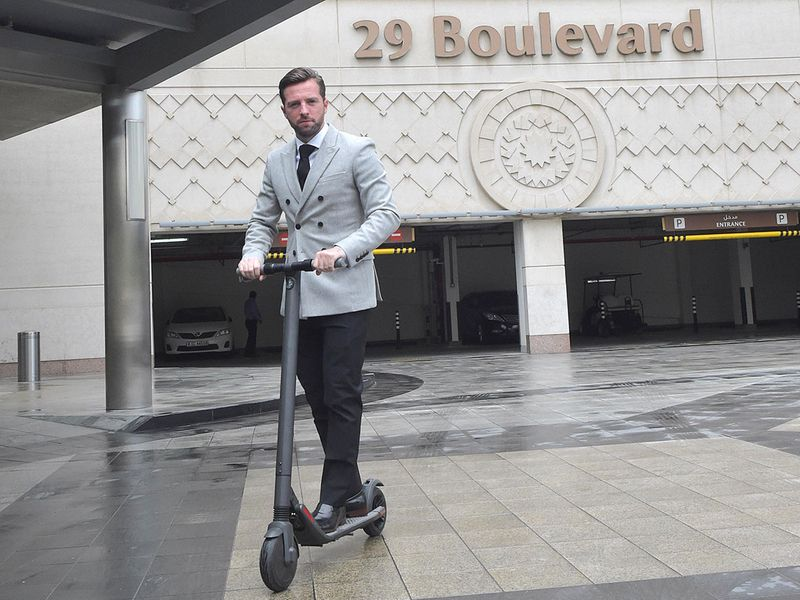 Neil Ormond with his electric scooter near his residence at Boulevard Downtown in Dubai.