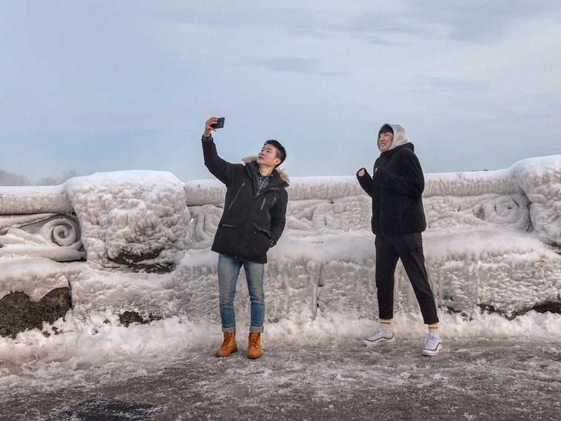 Visitors take a selfie as ice and snow coat a railing