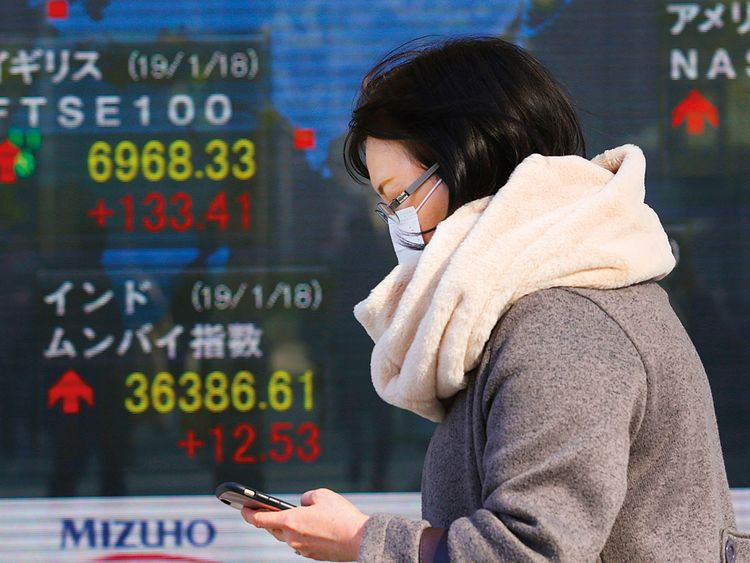 A woman walks by an electronic stock board