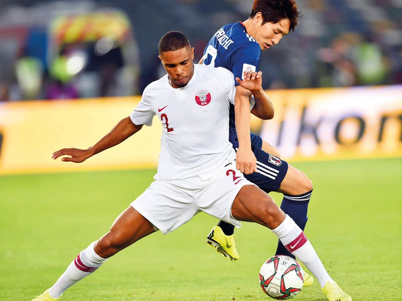 Qatar's player Redaq Koreah and Japan's Tamiyasu via for the ball
