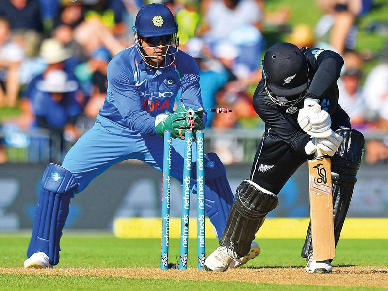 Mahendra Singh Dhoni (L) stumps New Zealand's Lockie Ferguson