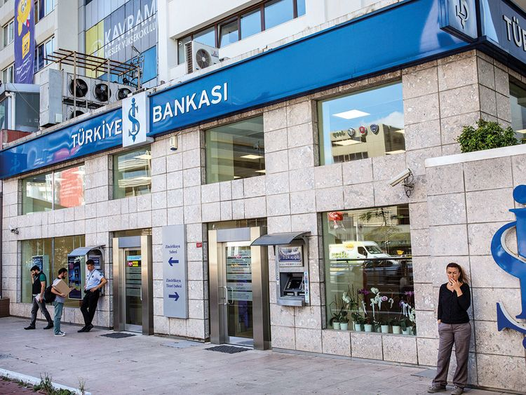People stand outside a branch of Turkiye Is Bankasi AS
