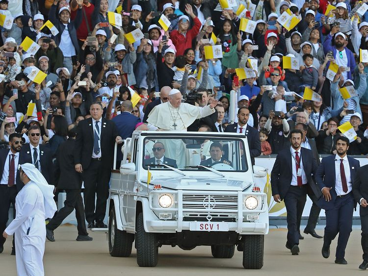 Pope Francis waves to the crowd as he arrives to lead mass