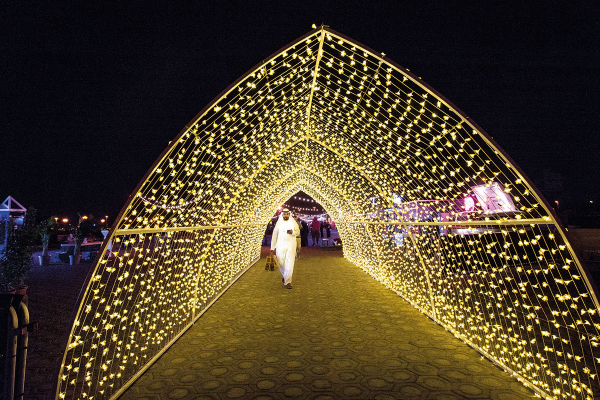 People take a walk under canopy of lights