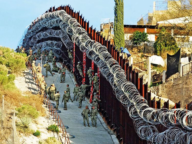 US Army troops install additional concertina wire