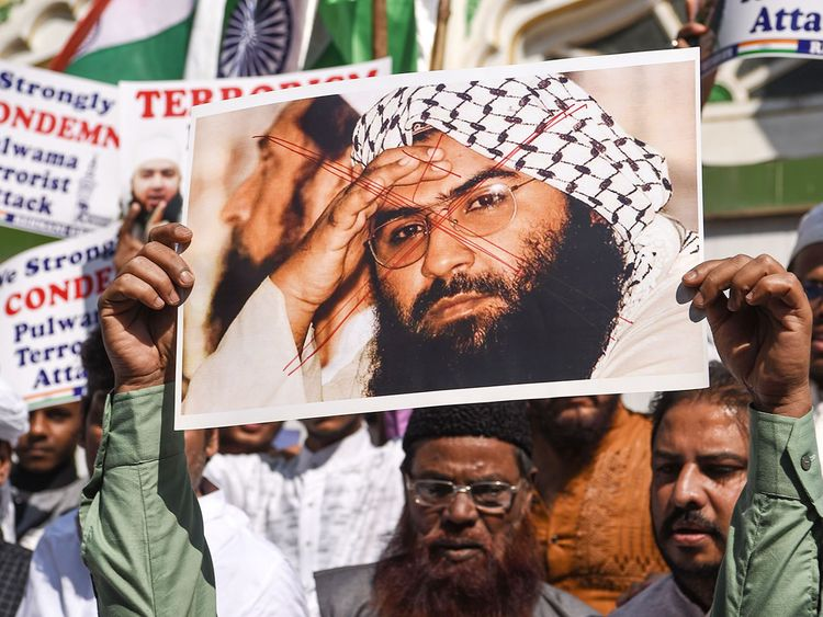 Protesters hold a scratched photo of Jaish-e-Mohammad group chief
