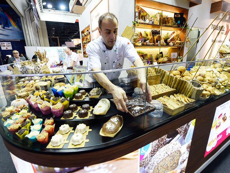 A chef arranges bakery products at Truebell stand