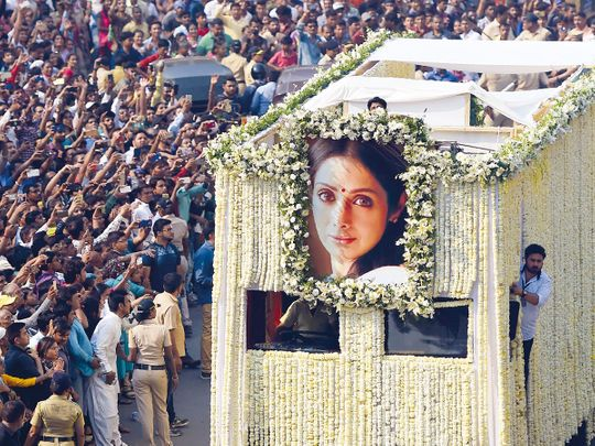 Fans watch as the funeral cortege for Sridevi passes through