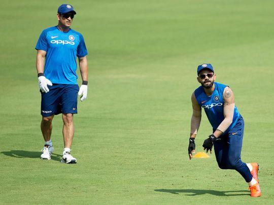 Mahendra Singh Dhoni, left, watches Virat Kohli