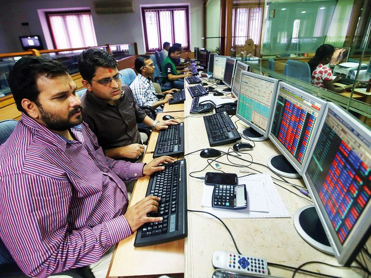 Traders work at a brokerage in Mumbai