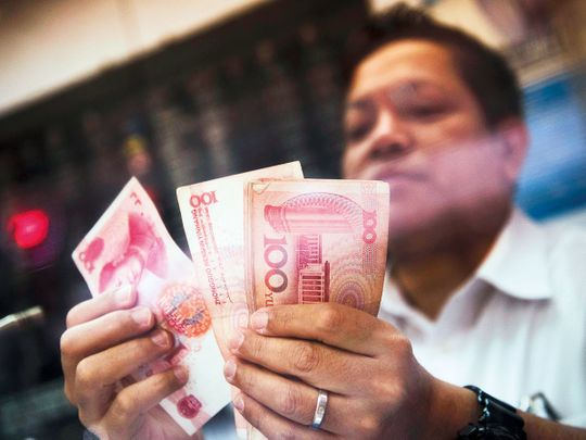 A currency exchange staff counts yuan notes in Hong Kong