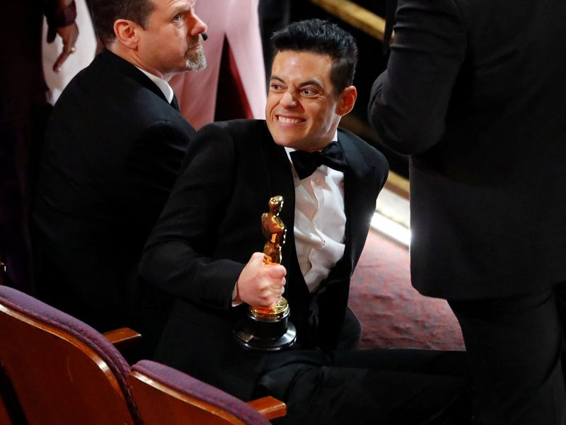 Rami Malek smiling in his seat