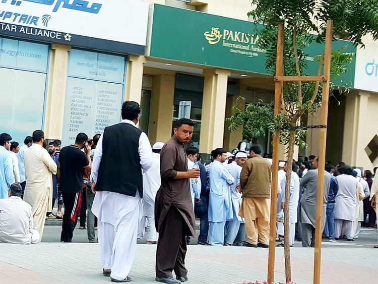 Scores of Pakistanis wait outside the PIA office