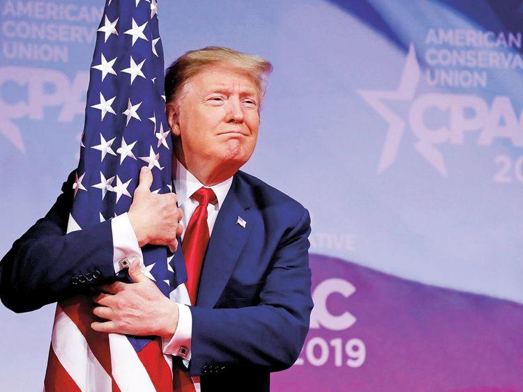 US President Donald Trump hugs American flag