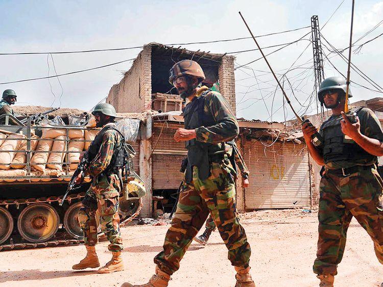 Pakistani soldiers patrol an empty bazaar