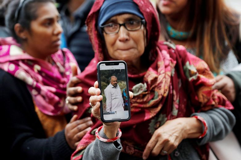 A woman holds up a photo of her husband 01