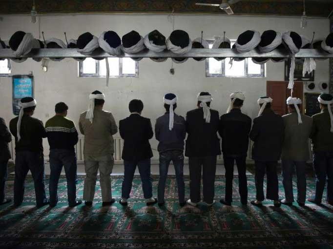 Uighur men pray in a mosque in Xinjiang 011