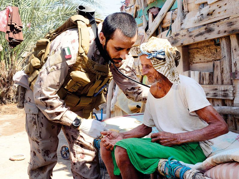 An UAE Armed Forces doctor checks an elderly Yemeni