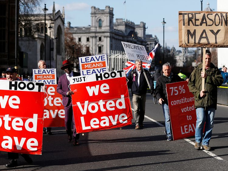 Pro-Brexit protesters walk outside the Houses of Parliament in London