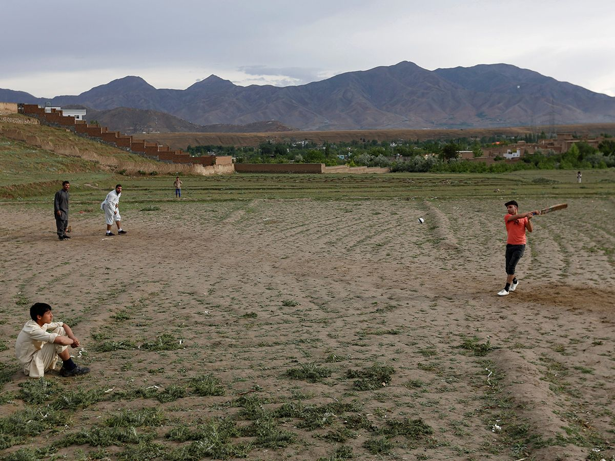 Afghan men play cricket on outskirt of Kabul