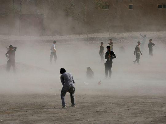 An Afghan boy wait for a brief dust storm