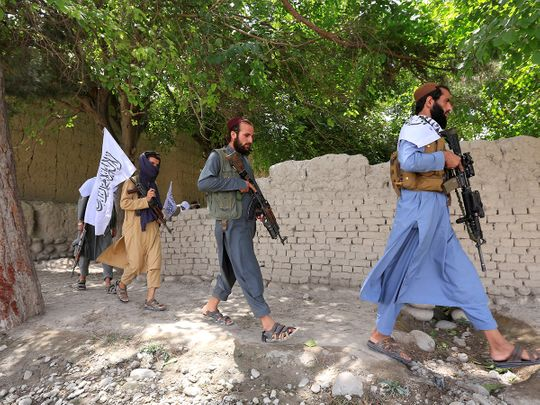 Taliban men walk as they celebrate ceasefire in Ghanikhel district