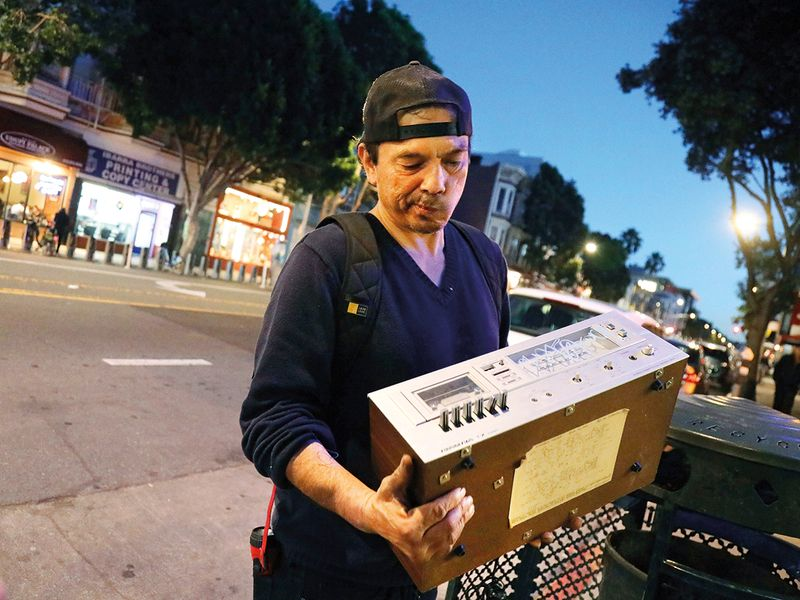 Jake Orta examines an old cassette tape deck