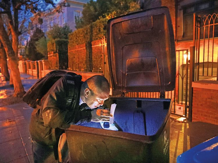 Jake Orta looks through a trash can