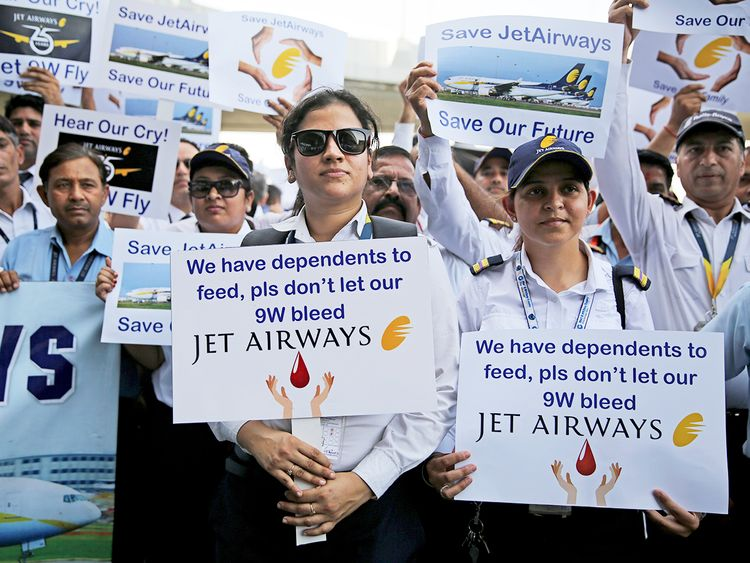 Employees of Jet Airways hold placards