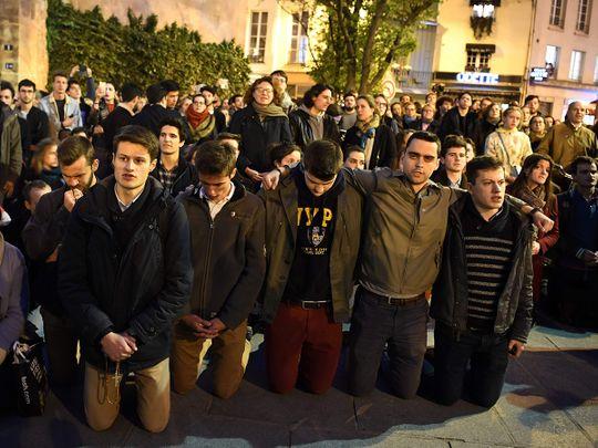 People kneel on the pavement