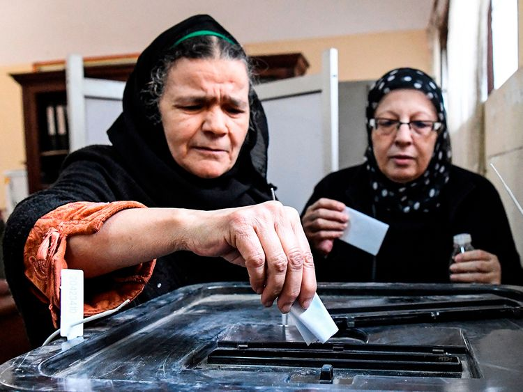 Egyptian women cast their ballots in a box